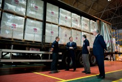UK PM David Cameron visits a 'UK AID' facility in Wiltshire. He stands in a warehouse with boxes marked UK AID.