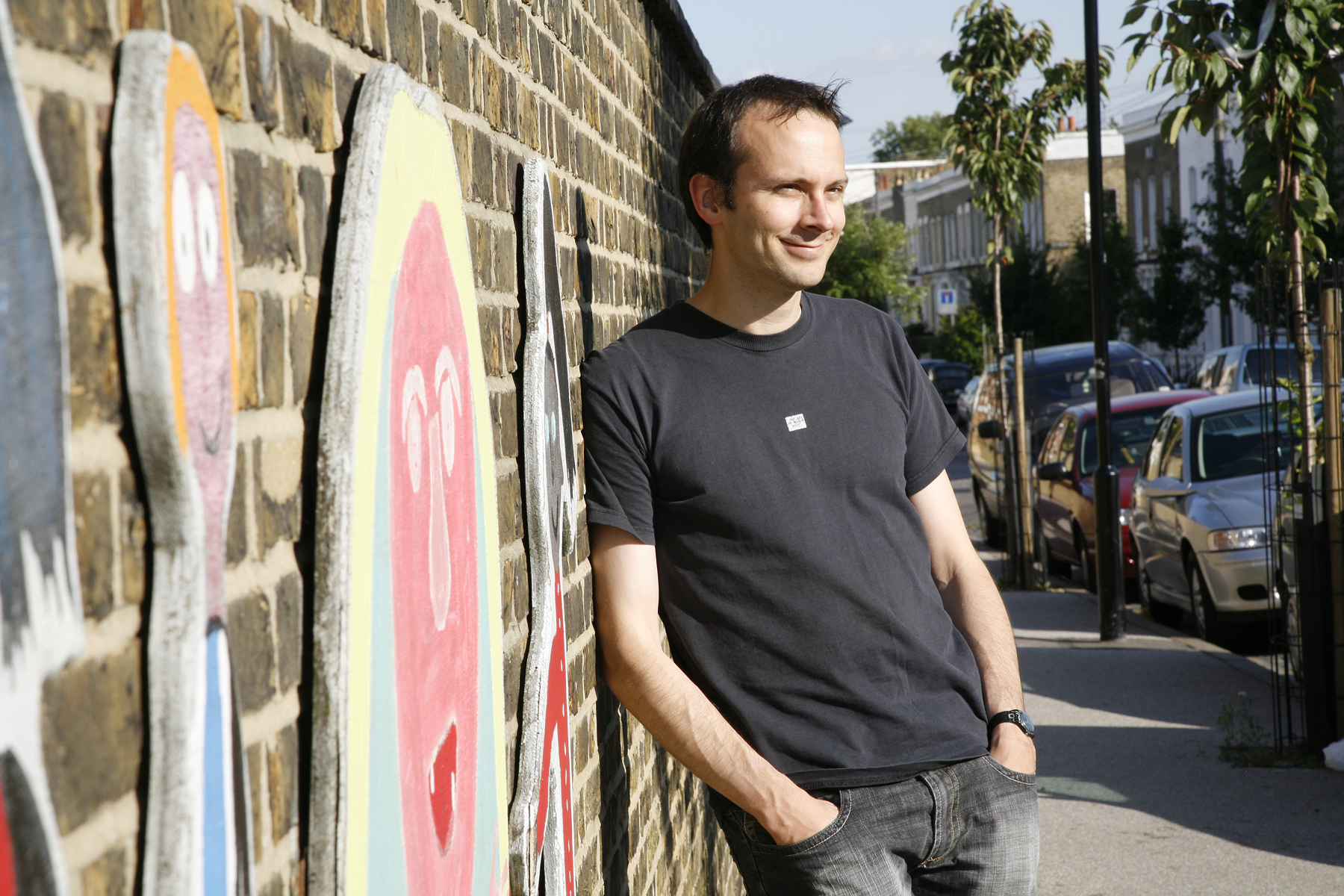 Tim Harford in black t-shirt and jeans, leaning against a wall with murals