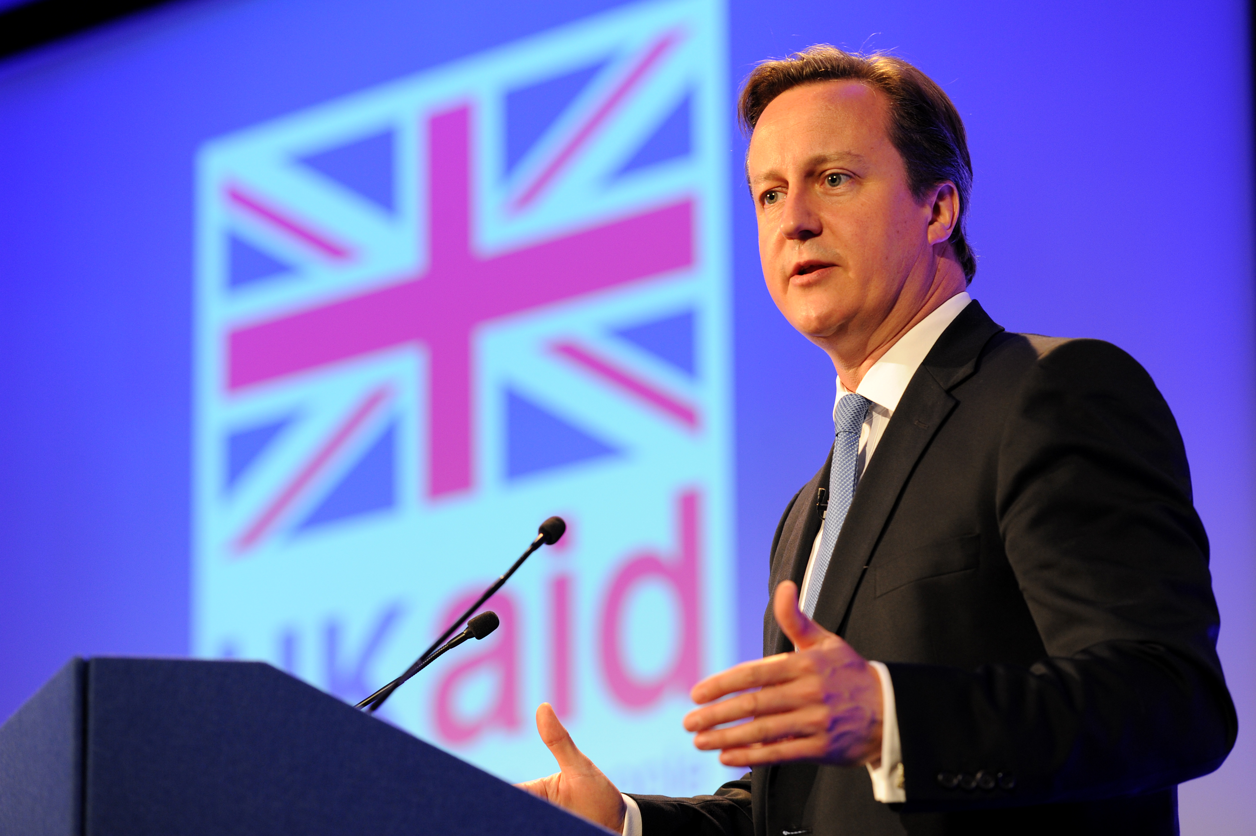 David Cameron at a podium in front of a UK Aid flag
