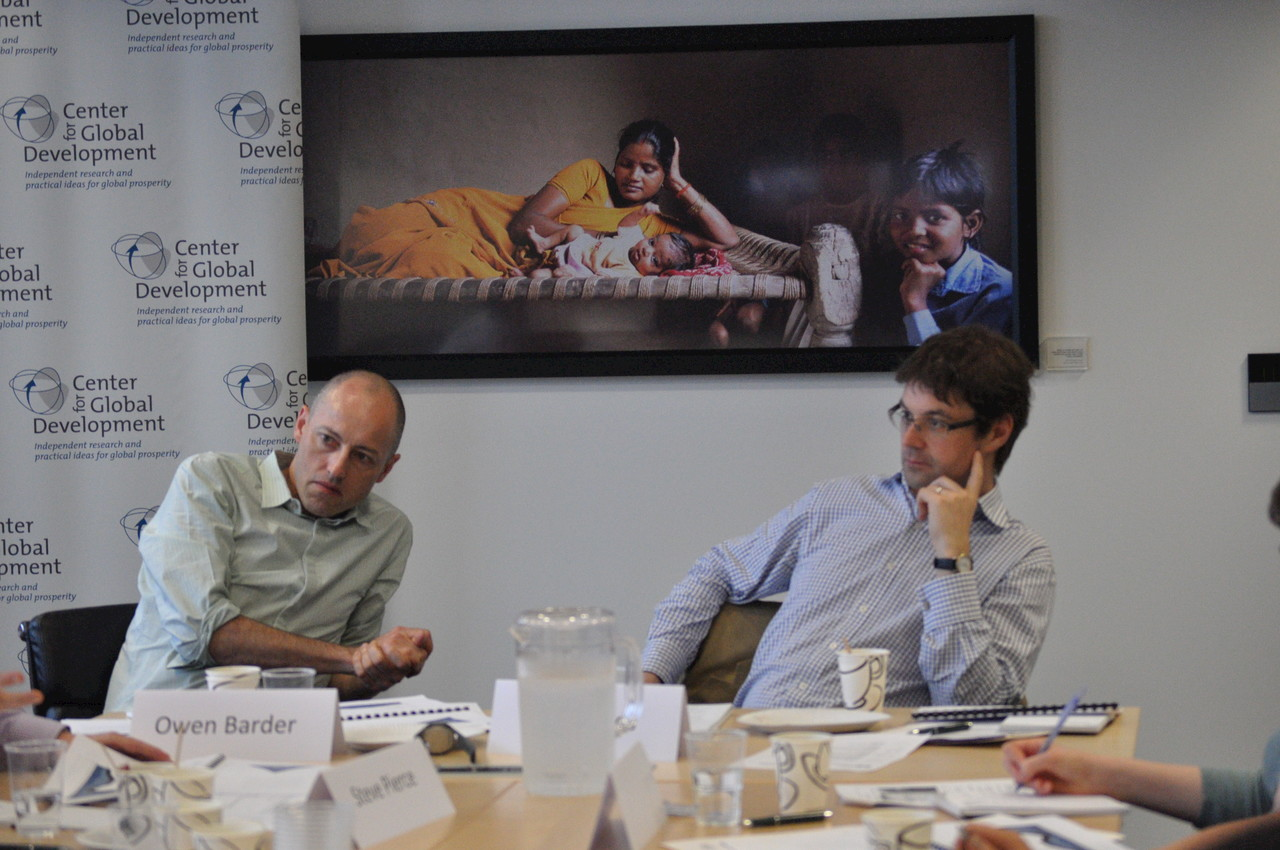 Owen Barder and Toby Eccles at the end of a conference table, with a picture of children behind them