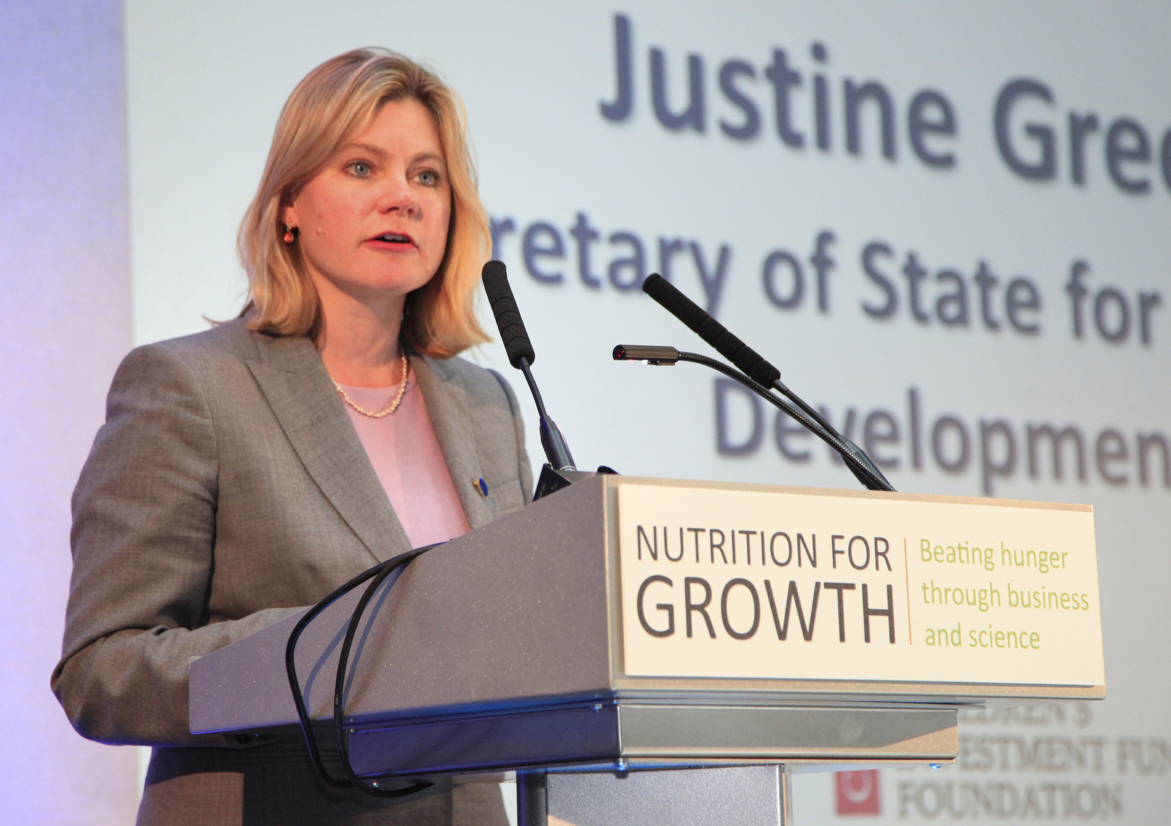 """Justine Greening, Secretary of State for International Development, at a podium labelled """"Nutrition for Growth"""""""