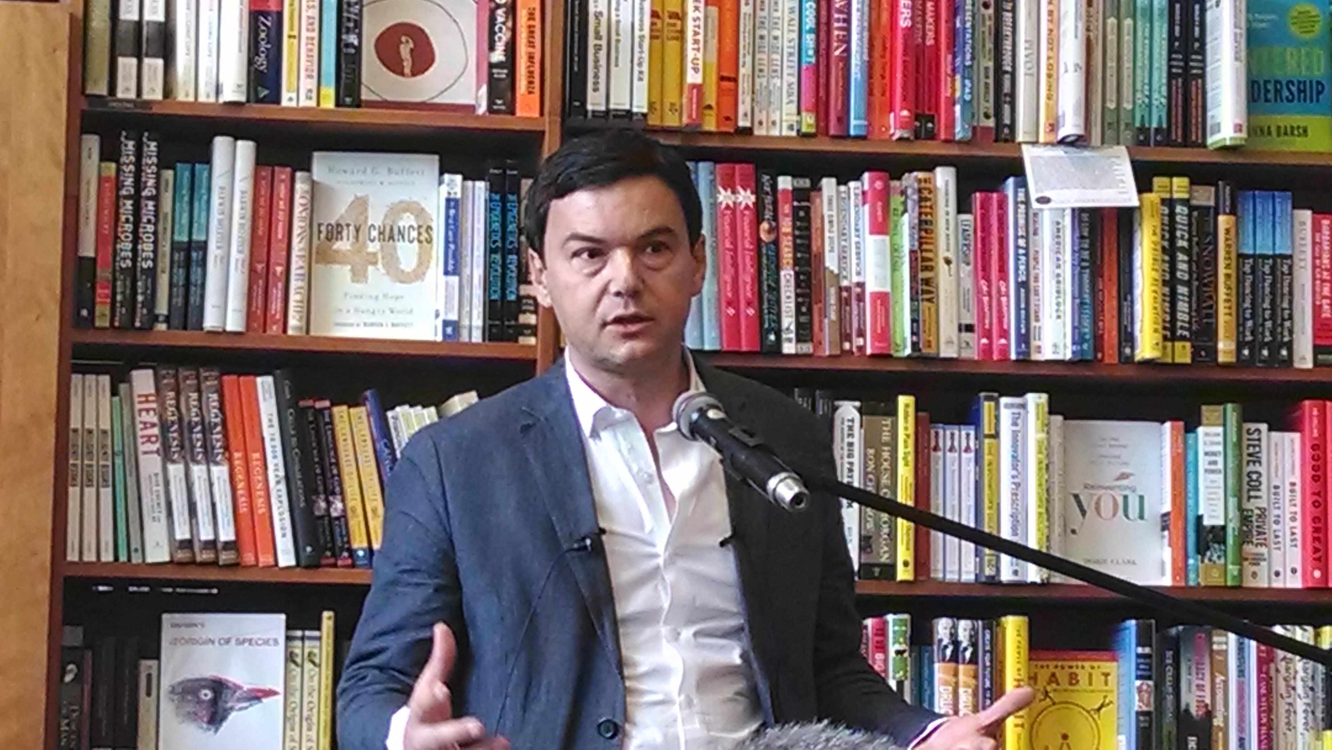 A picture of Thomas Piketty in front of a bookcase