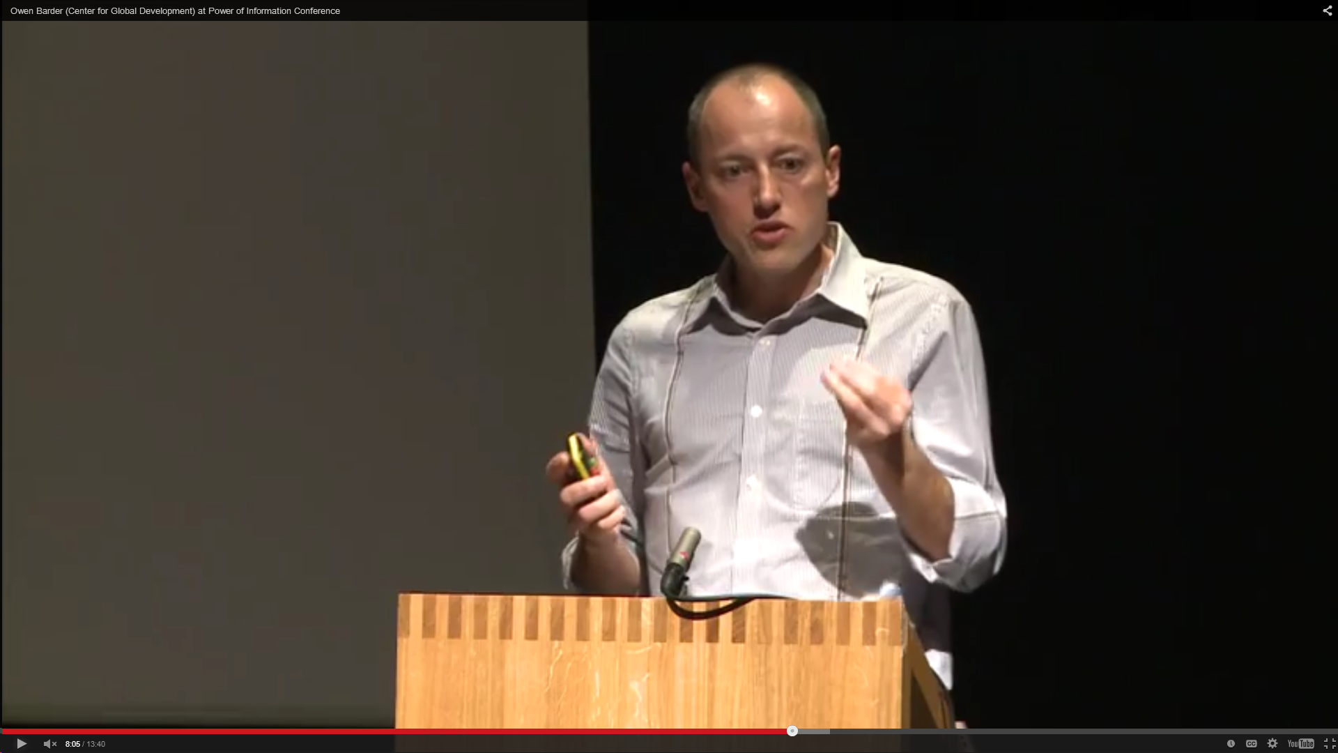 Owen Barder at a lectern, with a black backgroun. 2011