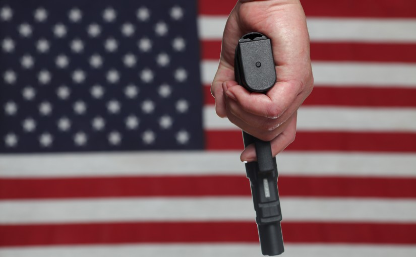 A hand gun in front of a US flag