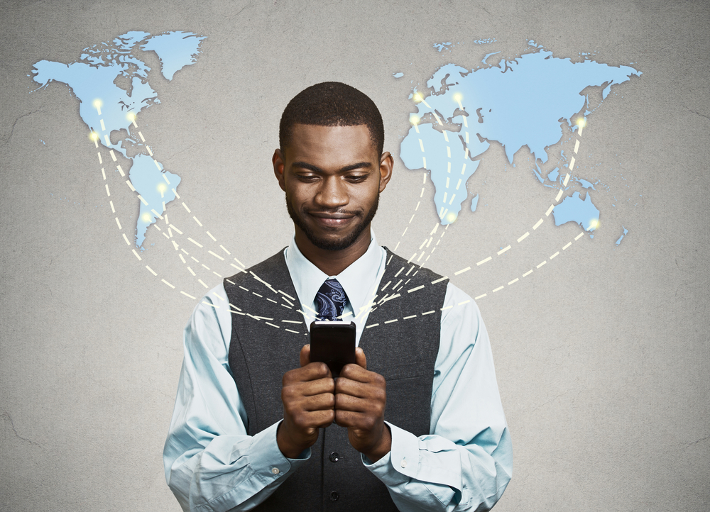 A man with a mobile phone in front of a world map