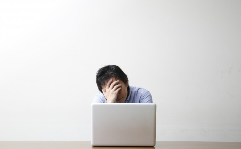 Depressed man by a laptop, white background