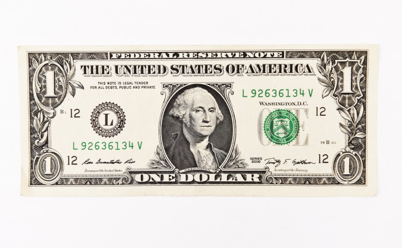 Close up of one dollar isolated on white background.