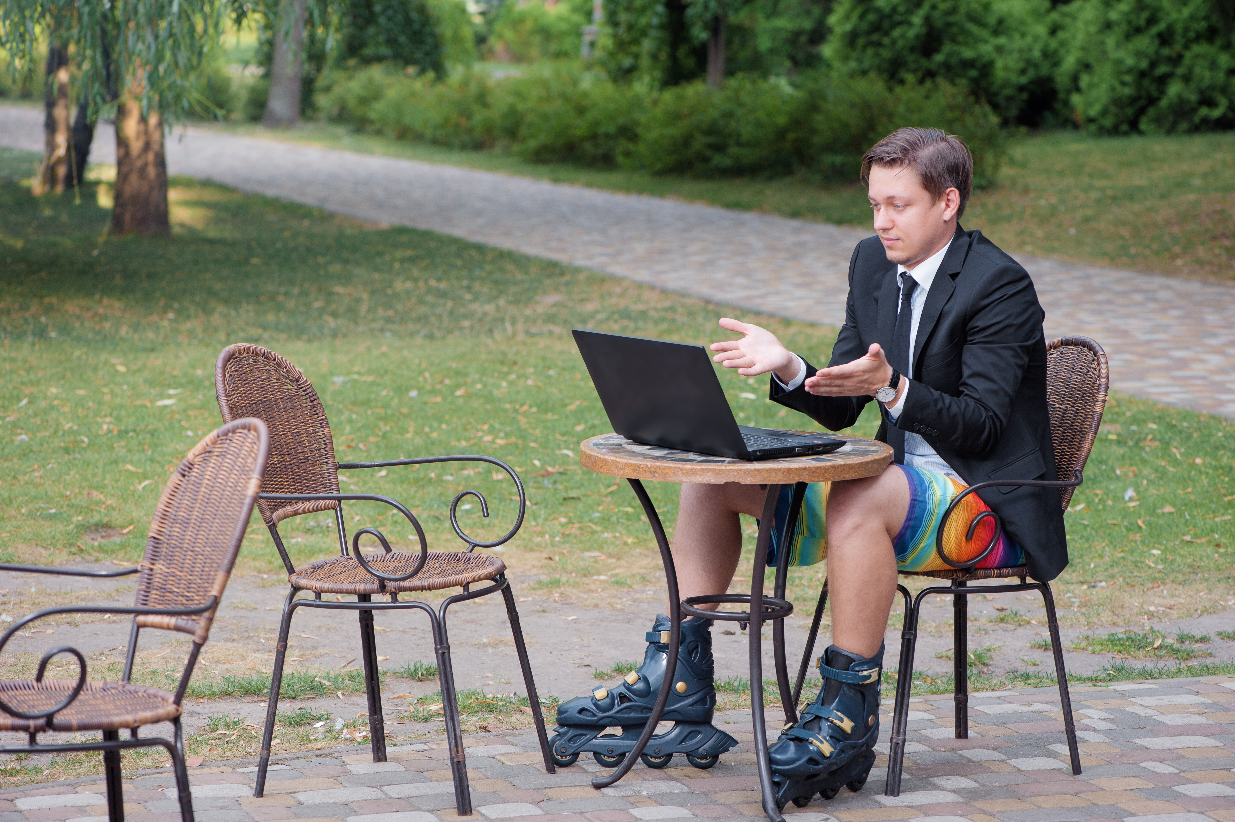Businessman dressed in suit and shorts working with laptop, talking by skype at the park cafe outdoors, wearing roller blades