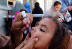 Health worker administrates polio-vaccine drops to a child during anti-polio immunization campaign at Pak-Afghan Border on April 08, 2015