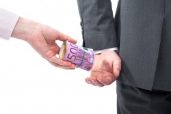 A businessman in a suit takes a bribe in Euros