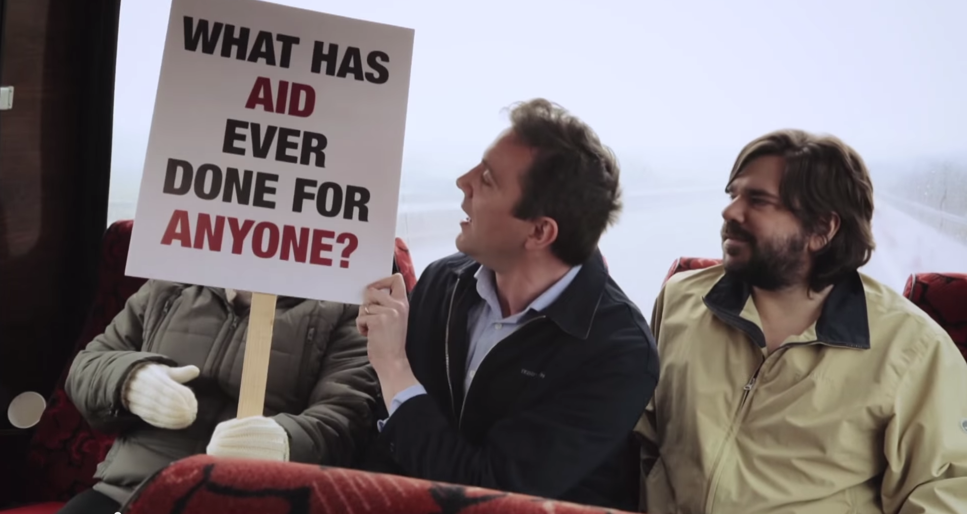 """A man holding a sign saying """"what has aid ever done for anyone?"""""""